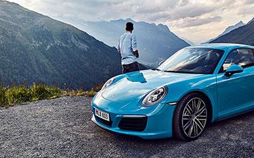 Blå Porsche parkerad på utkiksplats över bergen