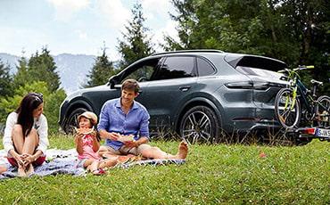 Familj på picknick. Porsche parkerad i bakgrunden,